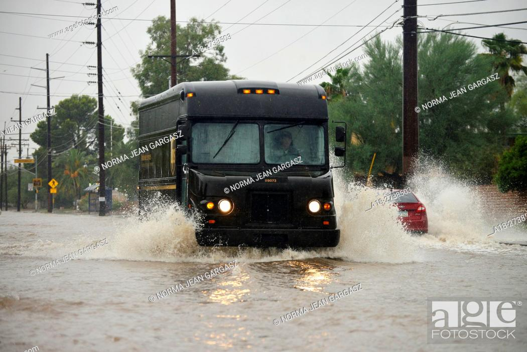 Stock Photo: An United Parcel Service delivery truck drives through flooded streets during a monsoon storm, Sonoran Desert, Tucson, Arizona, USA.