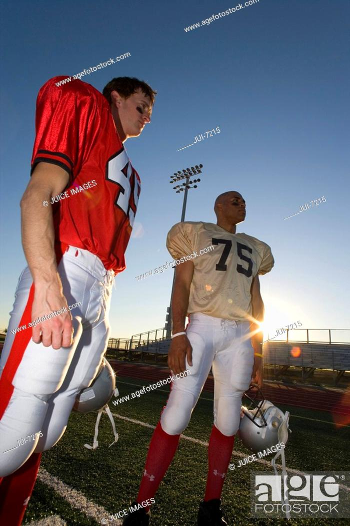 Stock Photo: Two American football players standing on pitch at sunset, low angle view lens flare, tilt.