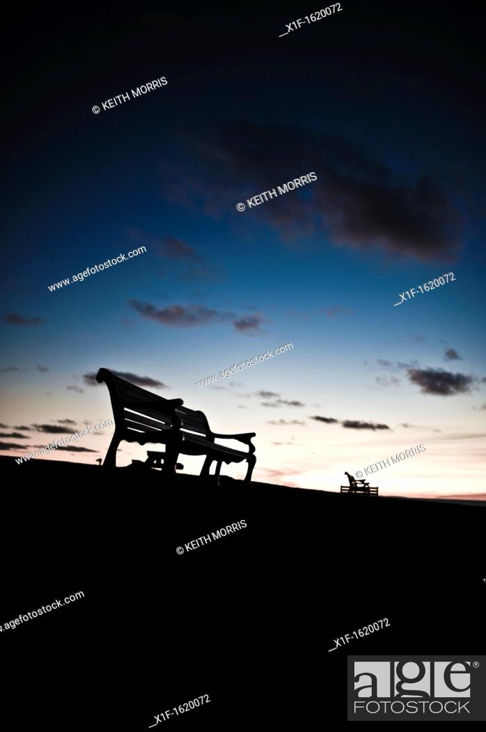 Stock Photo: Silhouettes of empty park benches against a twilight sky, UK.