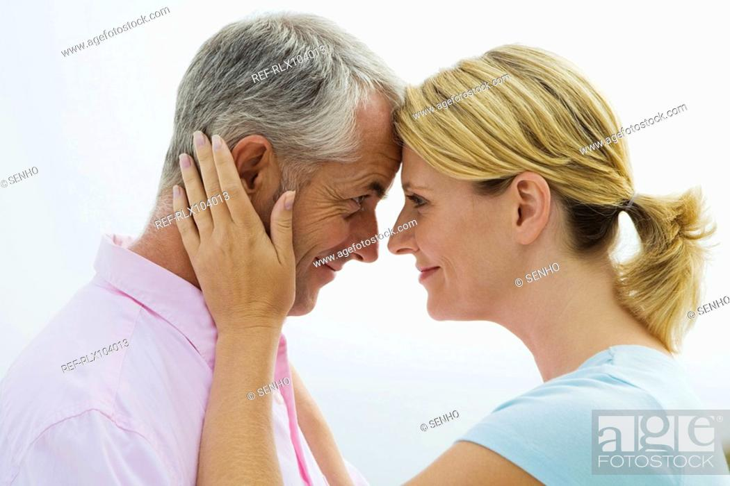 Stock Photo: Mature couple facing each other, smiling.