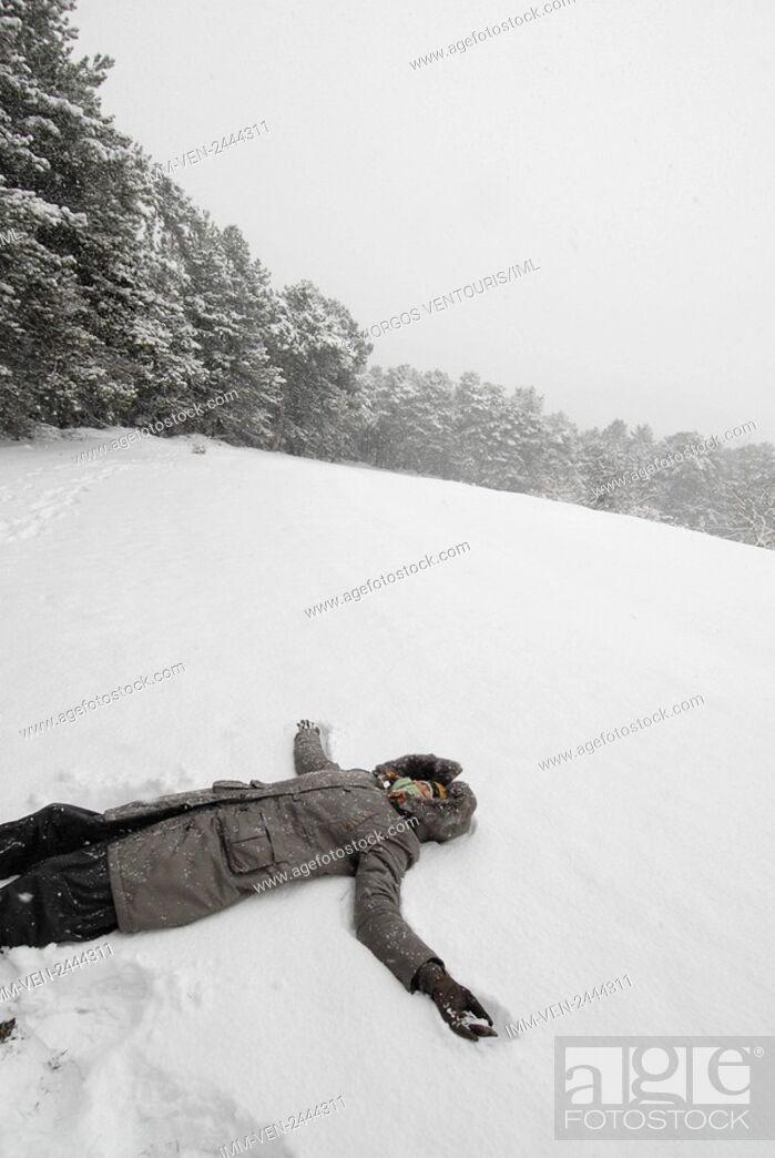 Stock Photo: Woman lying in the snow surrounding Doxa Lake. Doxa Laka, Feneo, Corinthia, Peloponnese, Greece.