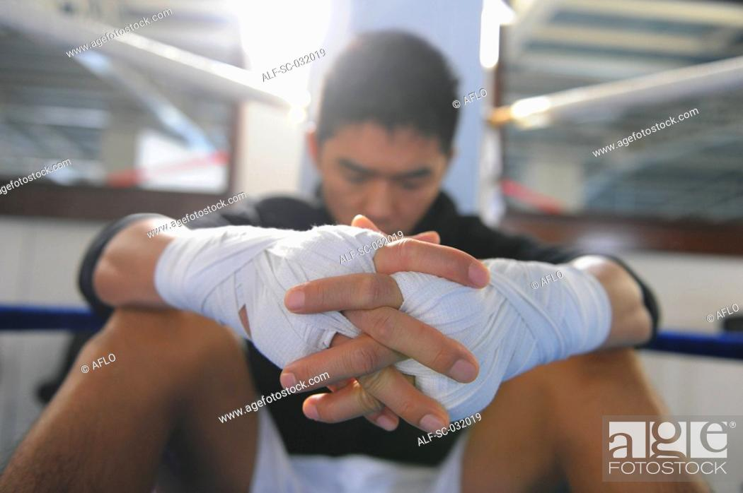 Stock Photo: Boxer wearing bandage in his both hands.