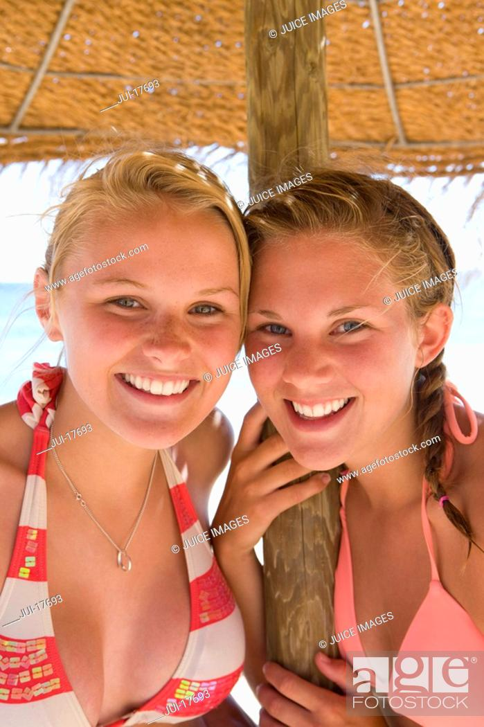 Stock Photo: Teenage girls posing under beach umbrella.