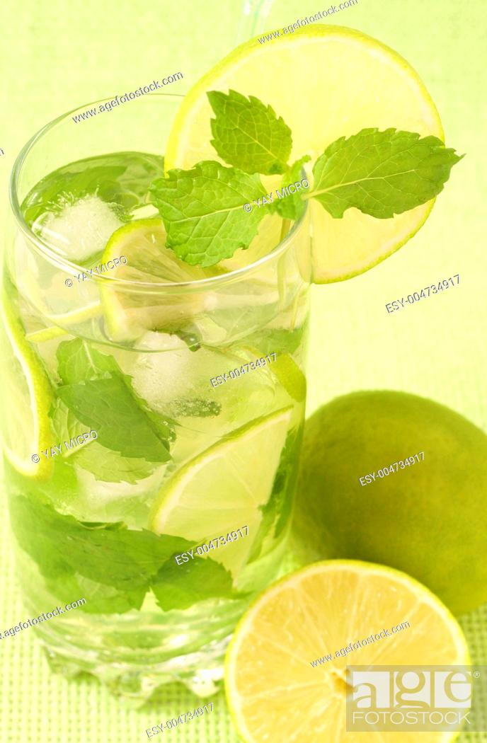 Stock Photo: Mojito cocktail on green background.