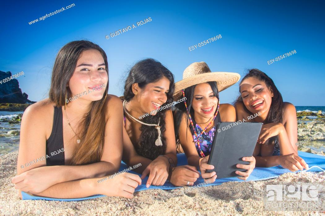 Stock Photo: four happy girls friends in summer clothes at the beach.