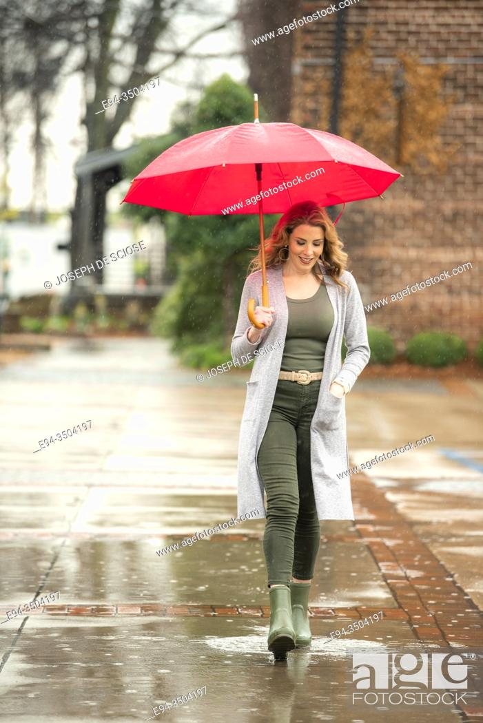 Stock Photo: A pretty 37 year old redheaded woman in an urban environment with an umbrella in the rain.