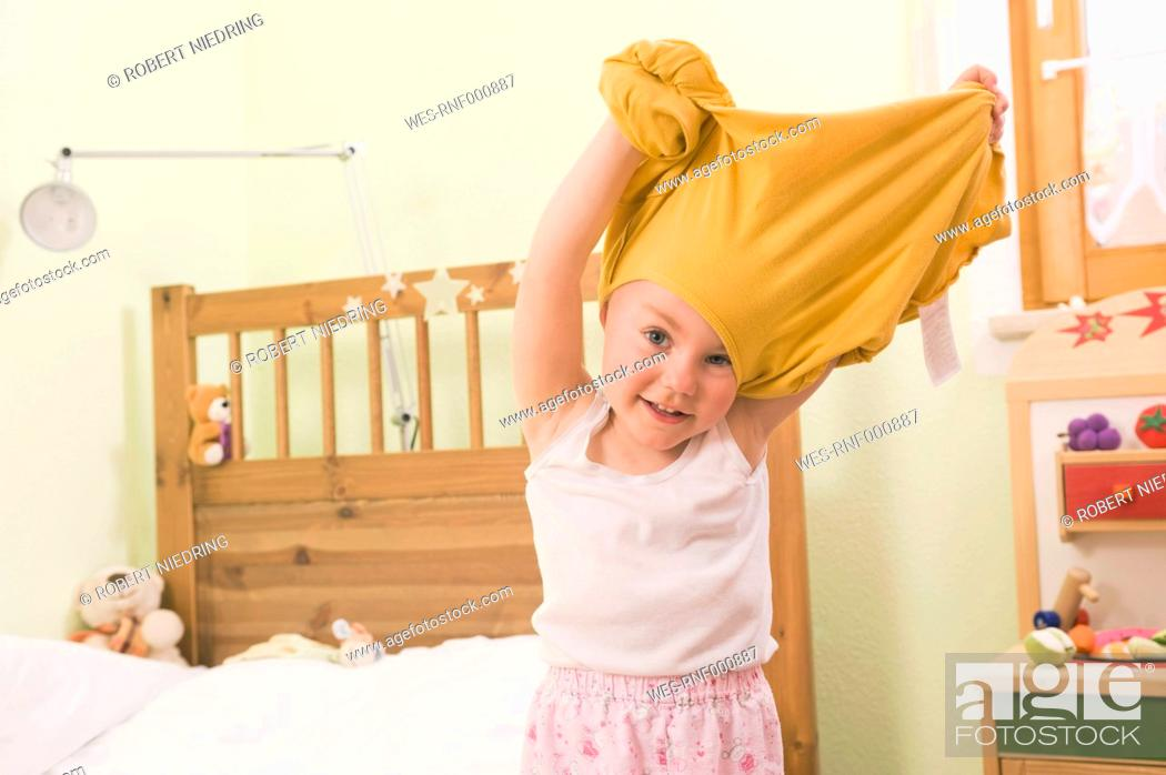 Stock Photo: Girl undressing, smiling, portrait.