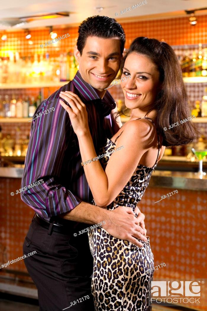 Stock Photo: Young couple embracing in bar, smiling, portrait.
