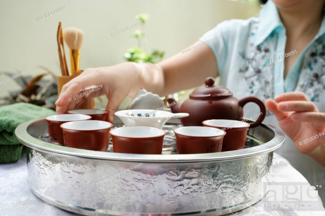 Imagen: Mid section view of a mid adult woman arranging tea cups in a serving tray.