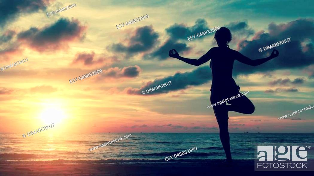 Stock Photo: Girl silhouette in yoga pose on the beach by the sea at sunset.