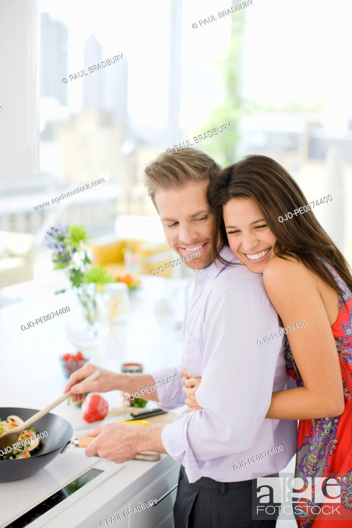 Stock Photo: Woman hugging husband while he's cooking in kitchen.