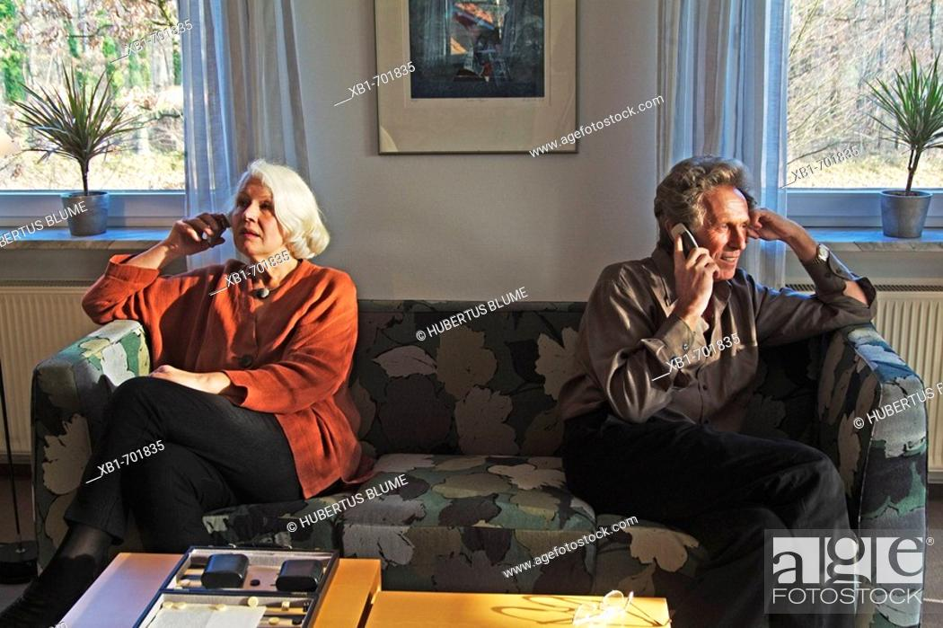 Stock Photo: Middleaged couple is sitting on a couch using their cellphones.