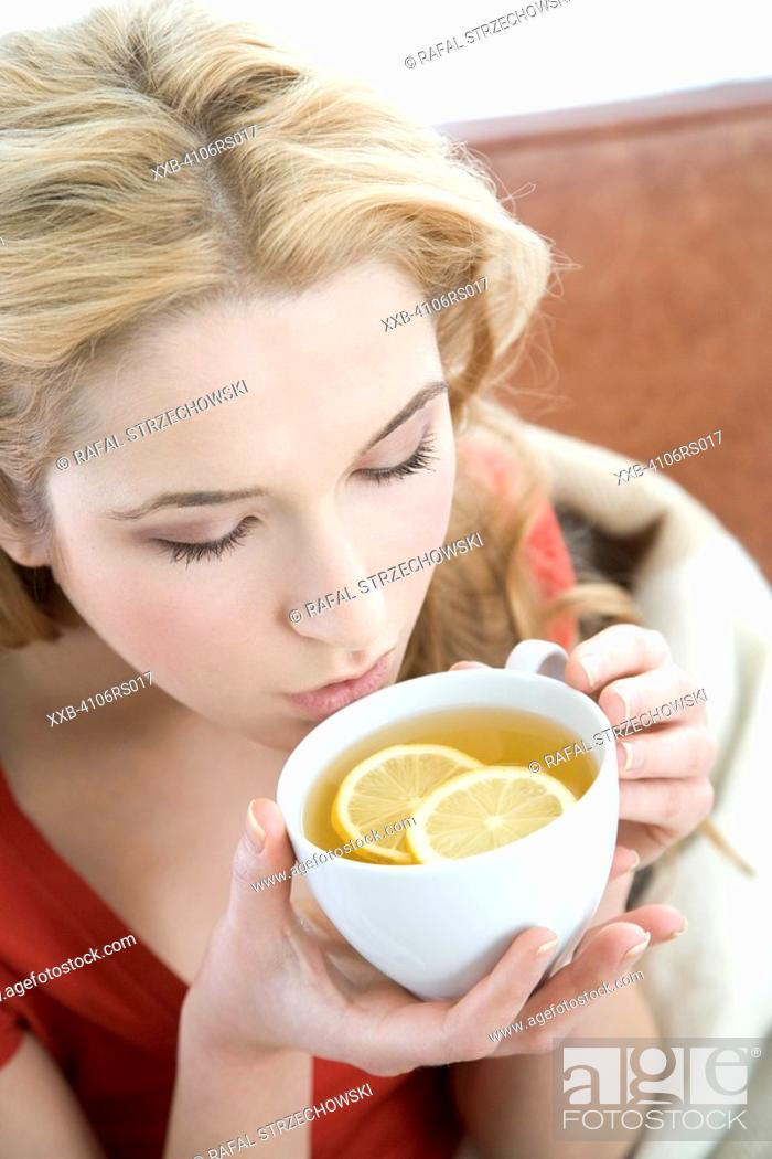 Stock Photo: woman drinking lemon tea.