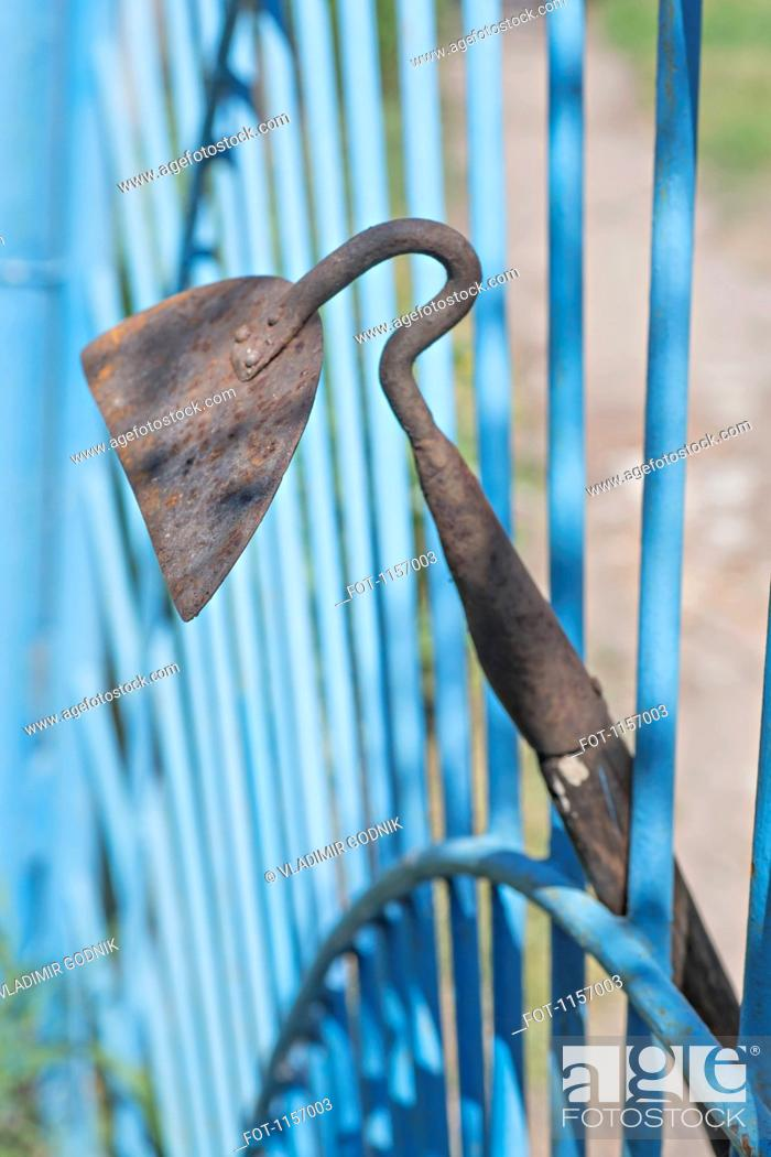 Stock Photo: A garden hoe leaning on a gate.