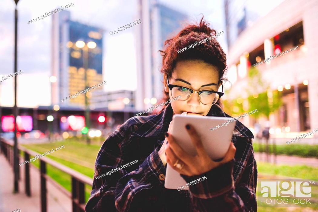 Stock Photo: Woman in urban area using digital tablet, Milan, Italy.