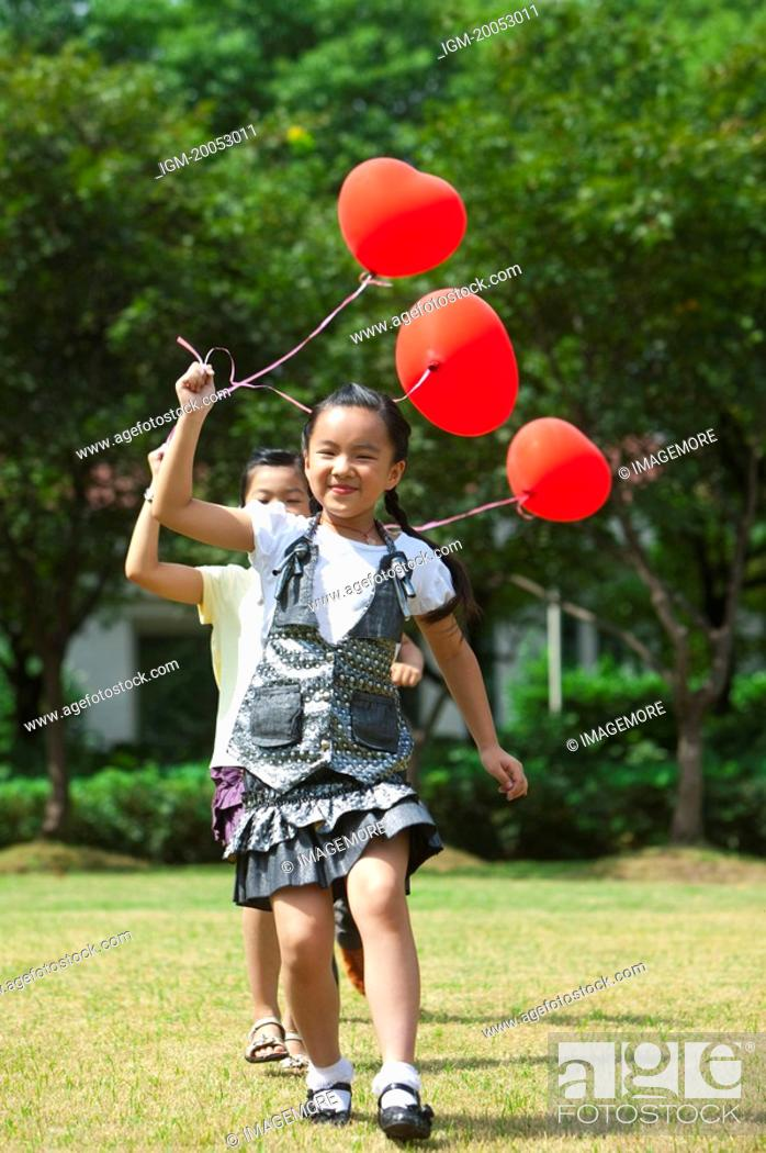 Stock Photo: Children holding balloon and running on the lawn together.