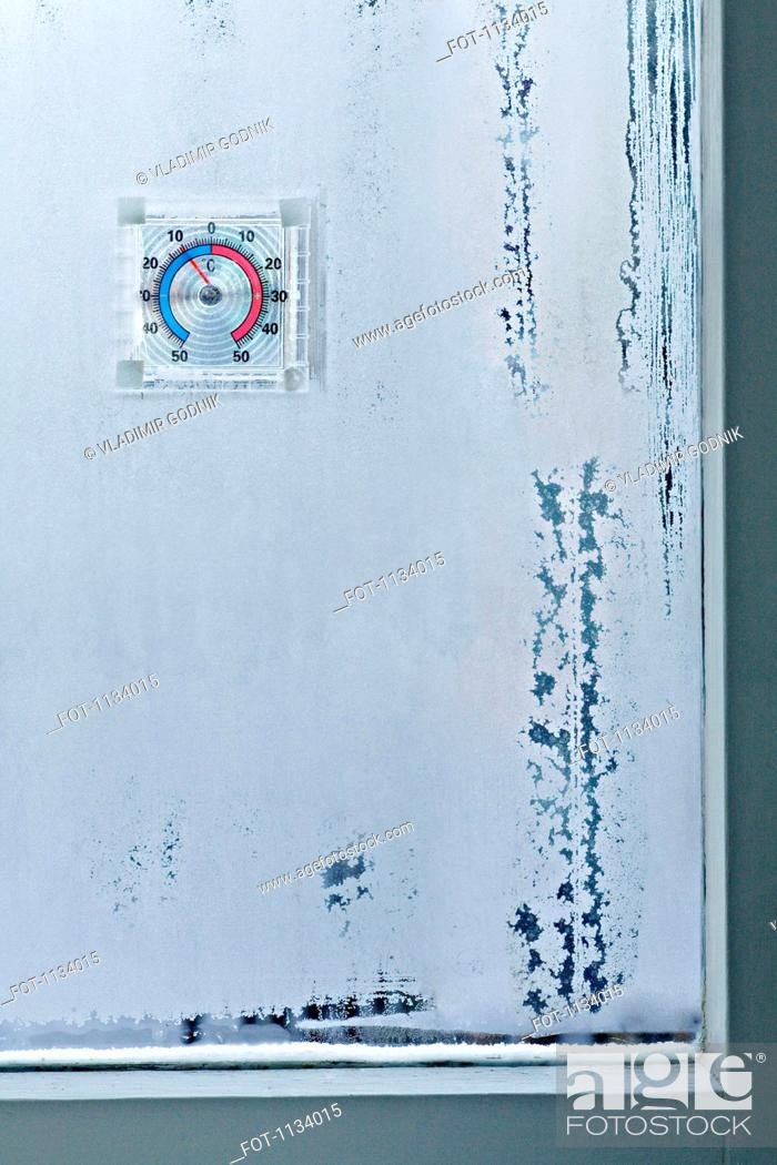 Stock Photo: Ice crystals on window and temperature gauge.
