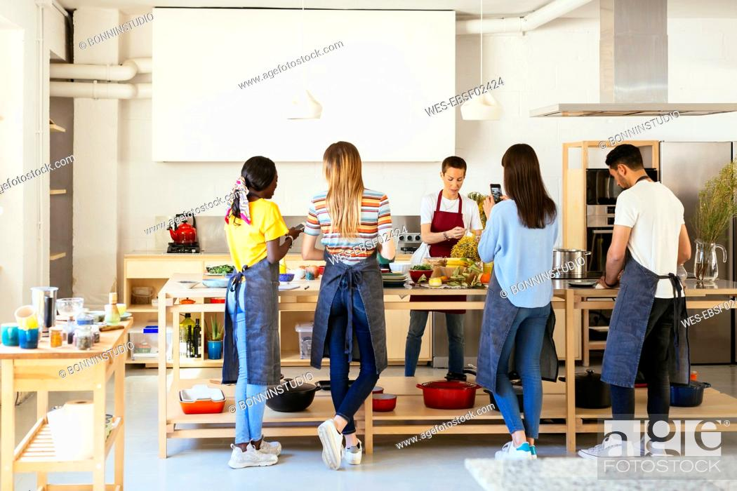 Stock Photo: Friends and instructor in a cooking workshop preparing food.