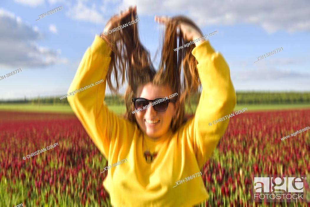 Photo de stock: Jeune femme facetieuse jouant avec ses longs cheveux pres d'un champ de trefle incarnat (Trifolium incarnatum) en fleur, Departement d'Eure-et-Loir.