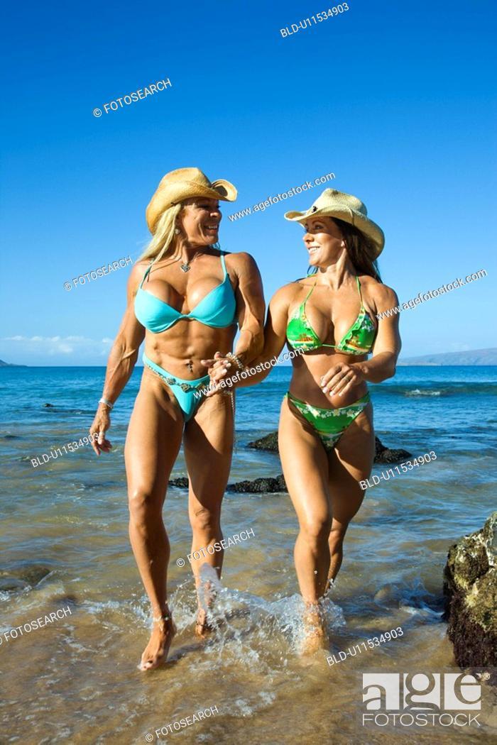 Stock Photo: Pretty Caucasian mid adult women bodybuilders in bikinis walking through water on beach.