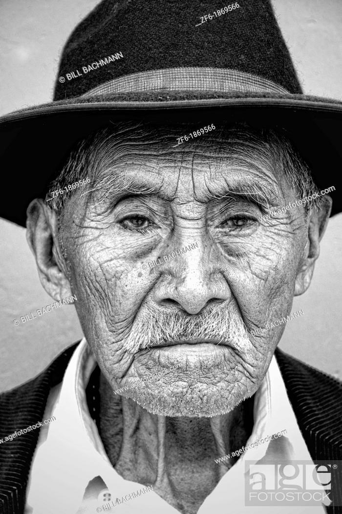 Stock Photo: Local black and white image of old man with wrinkles and great eyes against bright wall with black cowboy hat in tourist village of Antigua Guatemala.