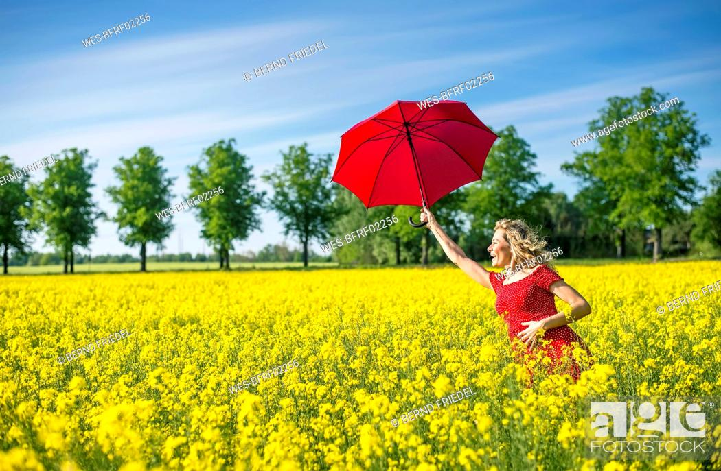 Stock Photo: Happy woman holding red umbrella while standing amidst oilseed rapes.