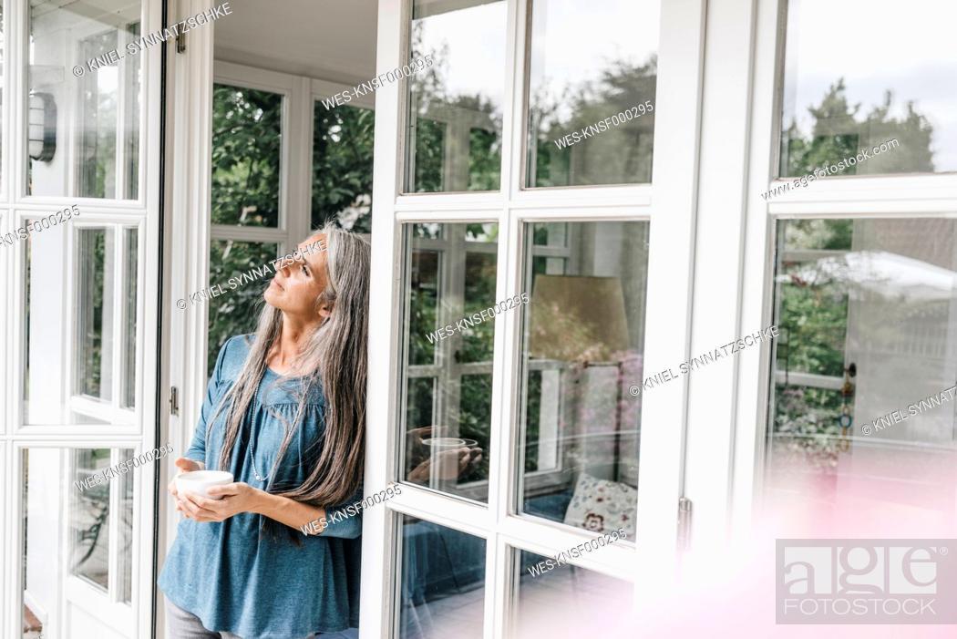 Stock Photo: Pensive woman leaning against door case of her winter garden.