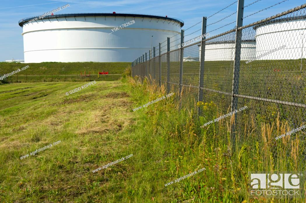 Stock Photo: Europoort, Rotterdam, Netherlands. Storage-tanks for oil, fuel and chemicals behind a meadow in Rotterdam harbor.