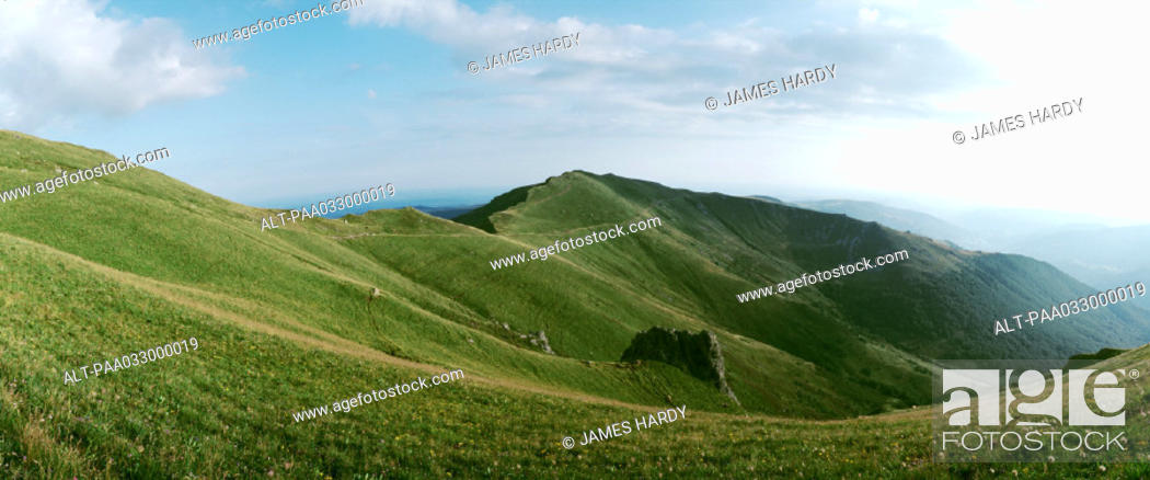 Stock Photo: France, grassy plateau, moutain ridge in background, panoramic view.