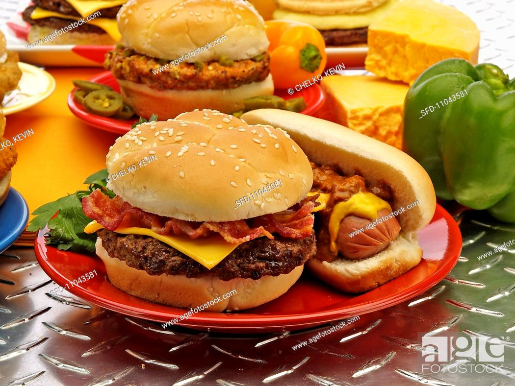 Stock Photo: Bacon Cheeseburger and Hotdog on a Red Plate, Cheese, Peppers and Burger in Background.