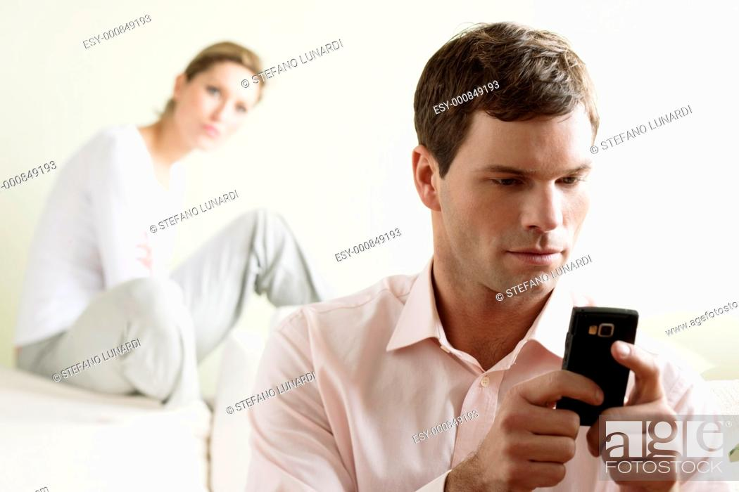 Stock Photo: Jealous woman looking at her partner chatting on the phone.