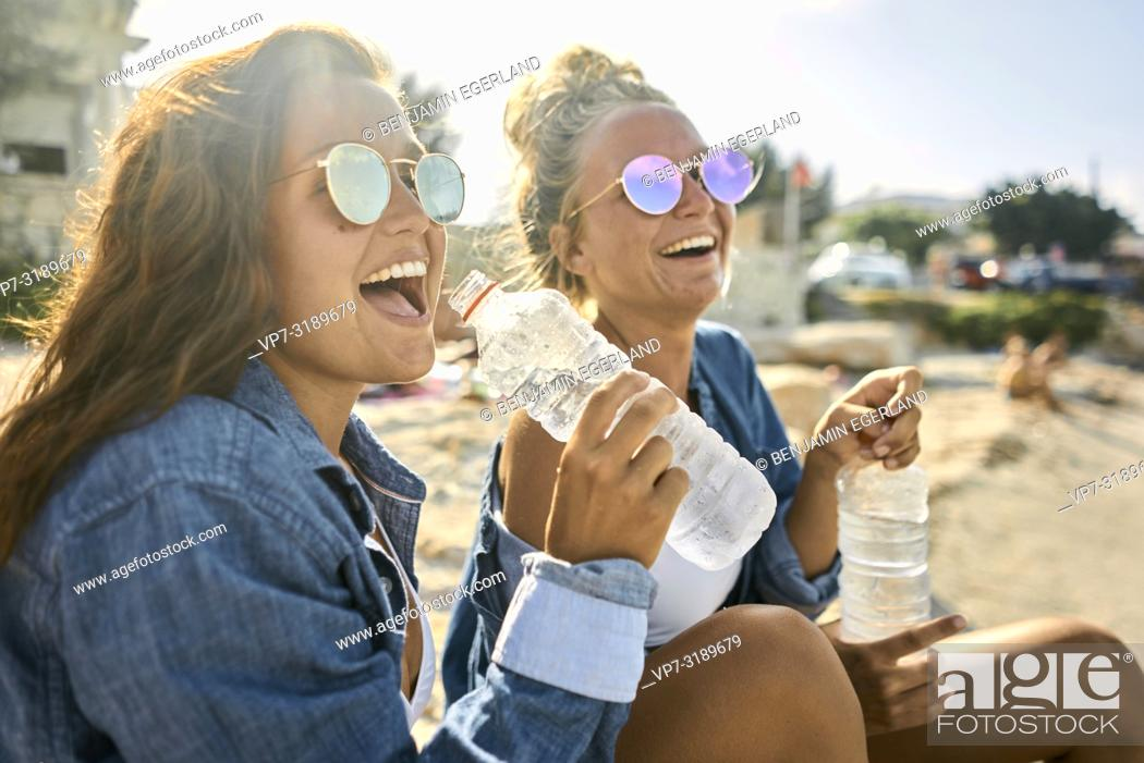 Stock Photo: Two women sitting at beach, Chersonissos, Crete, Greece.