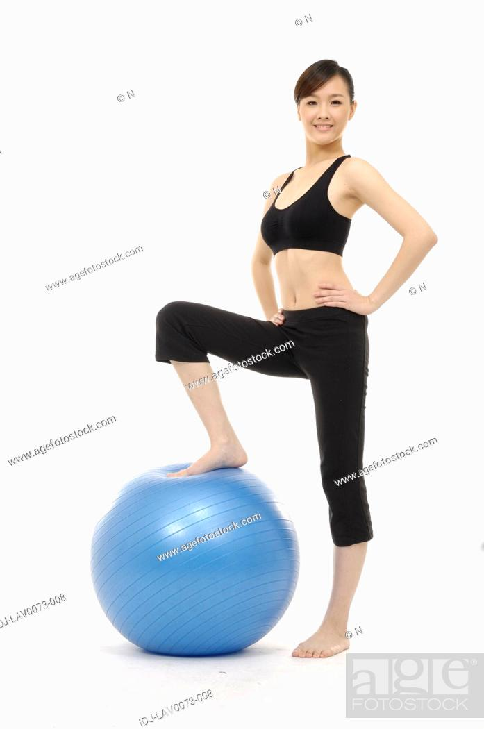 Stock Photo: Woman standing with one foot on large blue rubber ball.