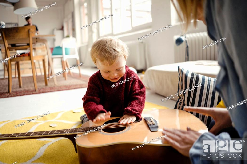 Imagen: Baby boy exploring a guitar with his mother.