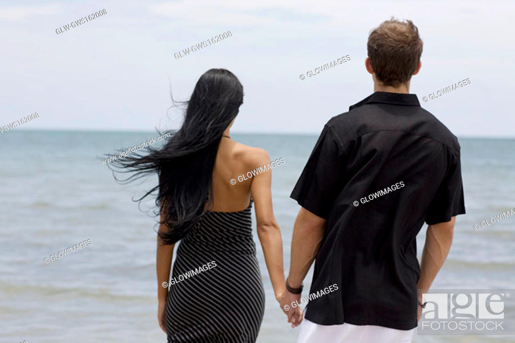 Stock Photo: Rear view of a young couple standing on the beach.