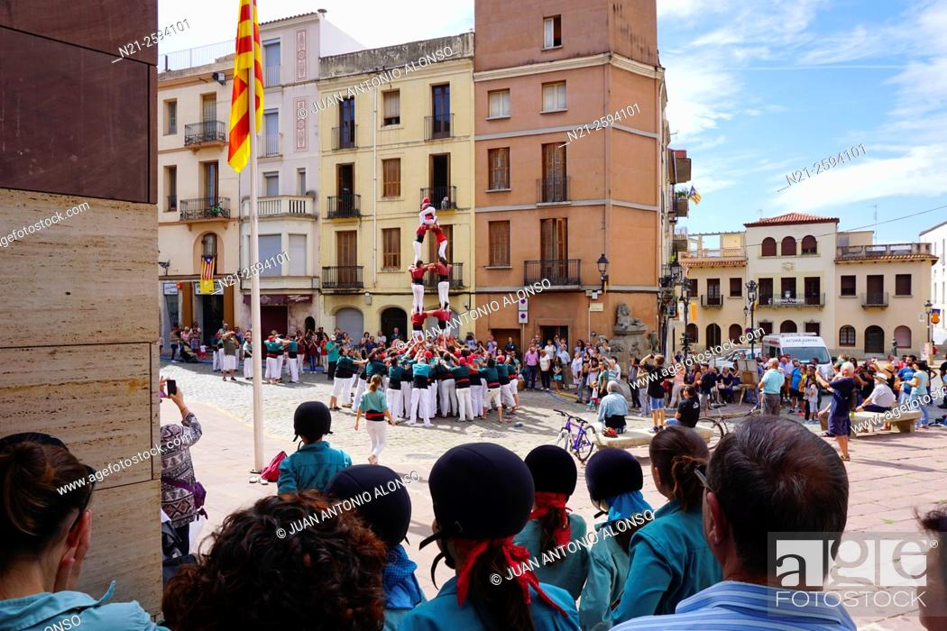 Stock Photo: Castellers building a traditionally Catalan human tower while a group of helmet-clad young girls -the ones who crown the tower- observe.