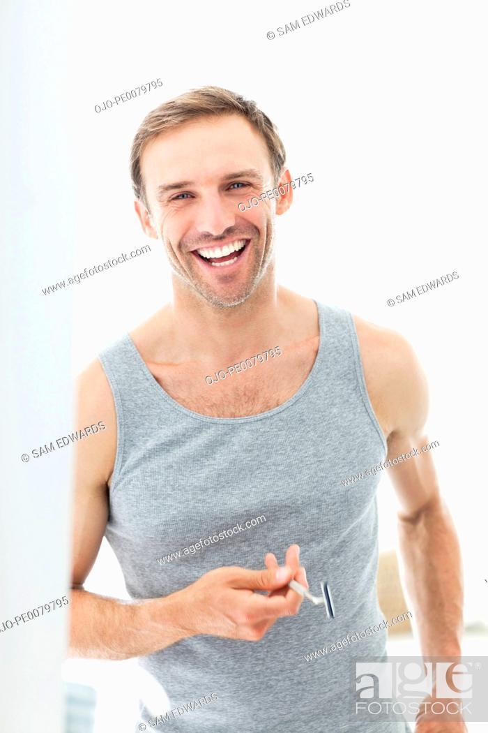 Stock Photo: Portrait of smiling man holding razor.