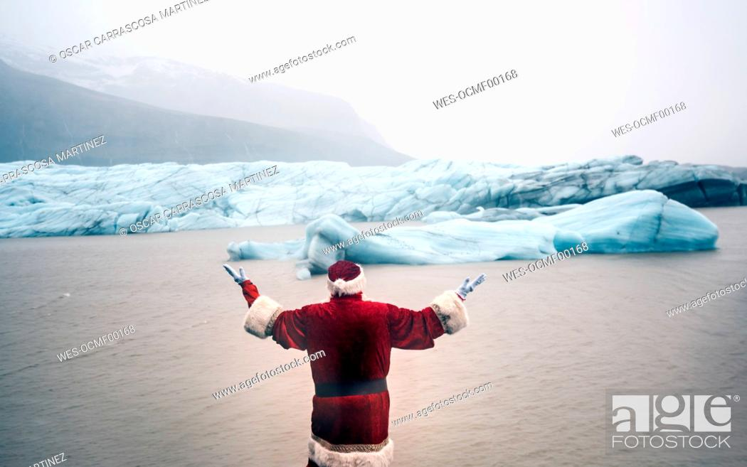 Stock Photo: Iceland, rear view of a man disguised as Santa Claus standing at a glacier raising his arms.