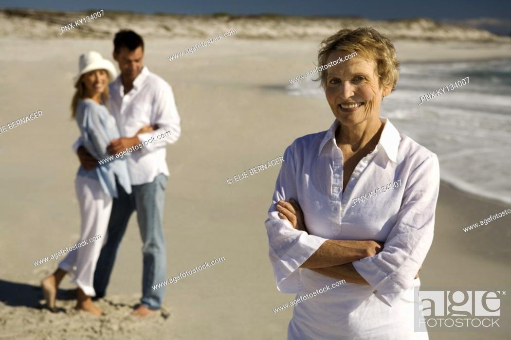 Stock Photo: Couple embracing and senior woman on the beach.