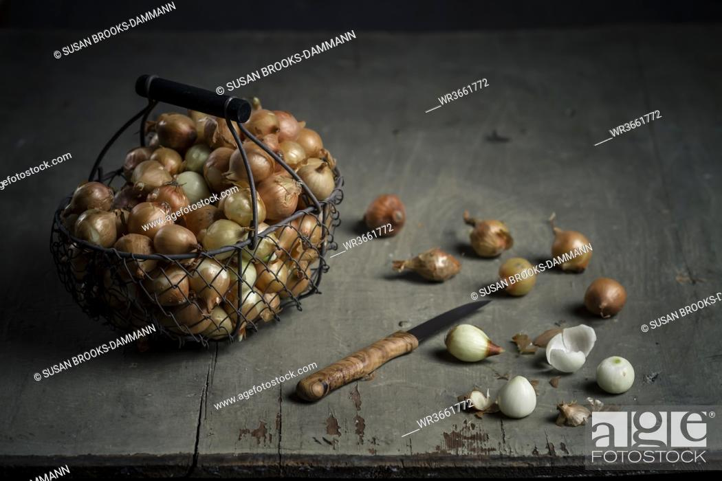 Stock Photo: Basket of pearl onions with knife on wooden board, close up.
