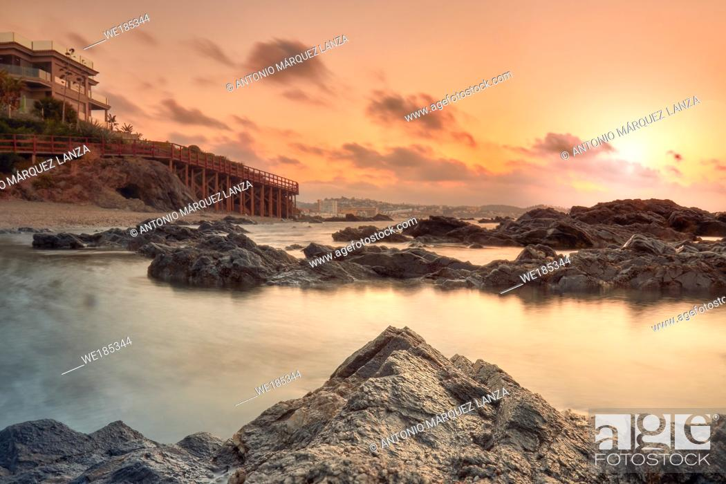 Stock Photo: Sunrise at the beach in Marbella with rocks and house.