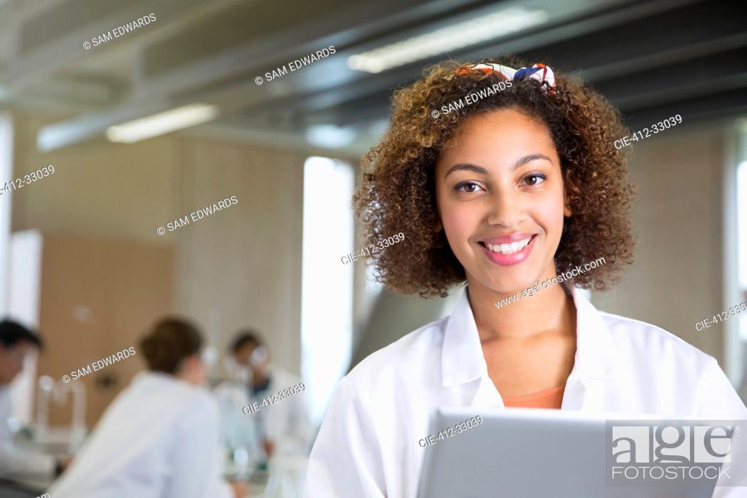 Stock Photo: Portrait smiling college student with digital tablet in science laboratory classroom.