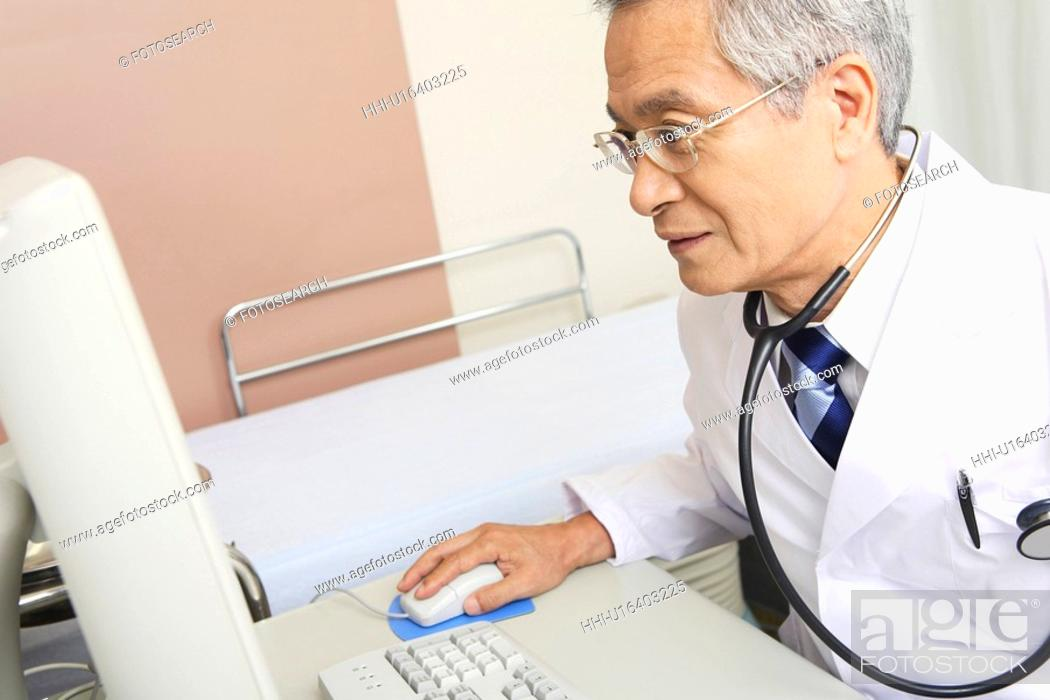 Stock Photo: Physician operating a PC.