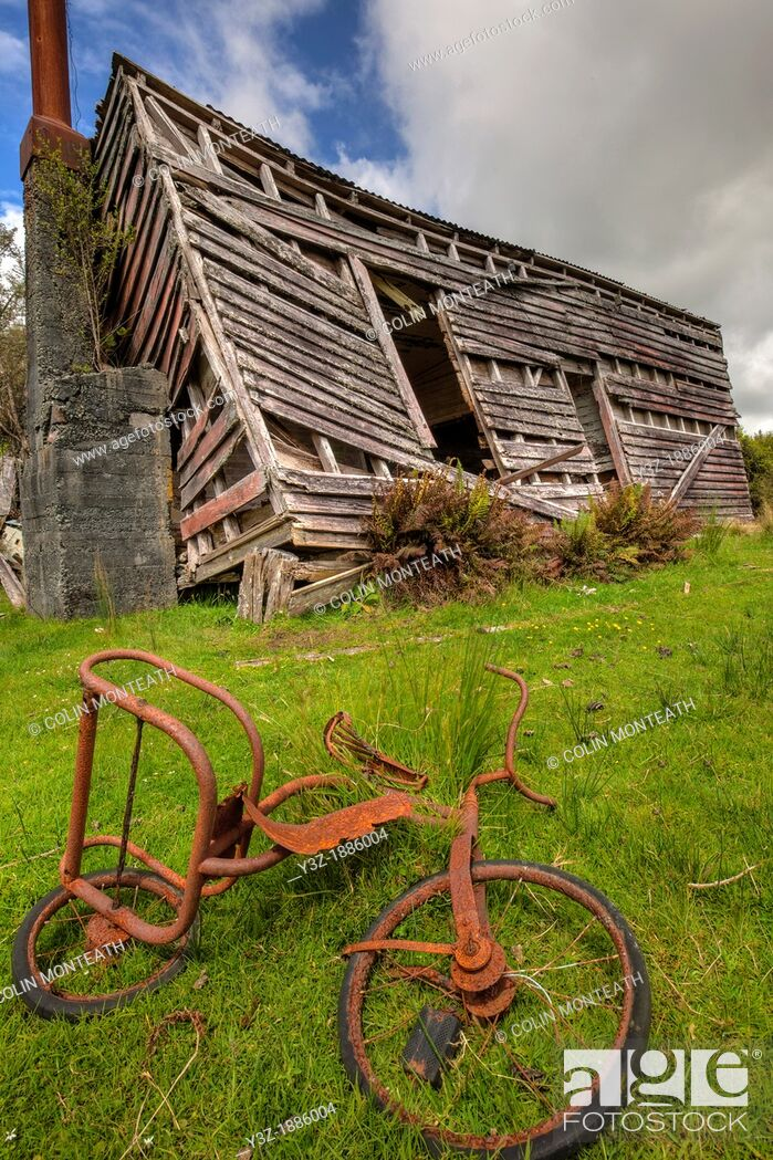 Stock Photo: Rusty child's tricycle in front of derelict shed, Kumara, West Coast, New Zealand.