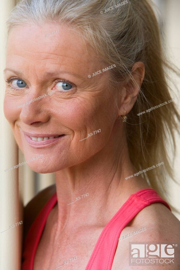 Stock Photo: Active senior woman wearing pink sports vest, smiling, close-up, side view, portrait.