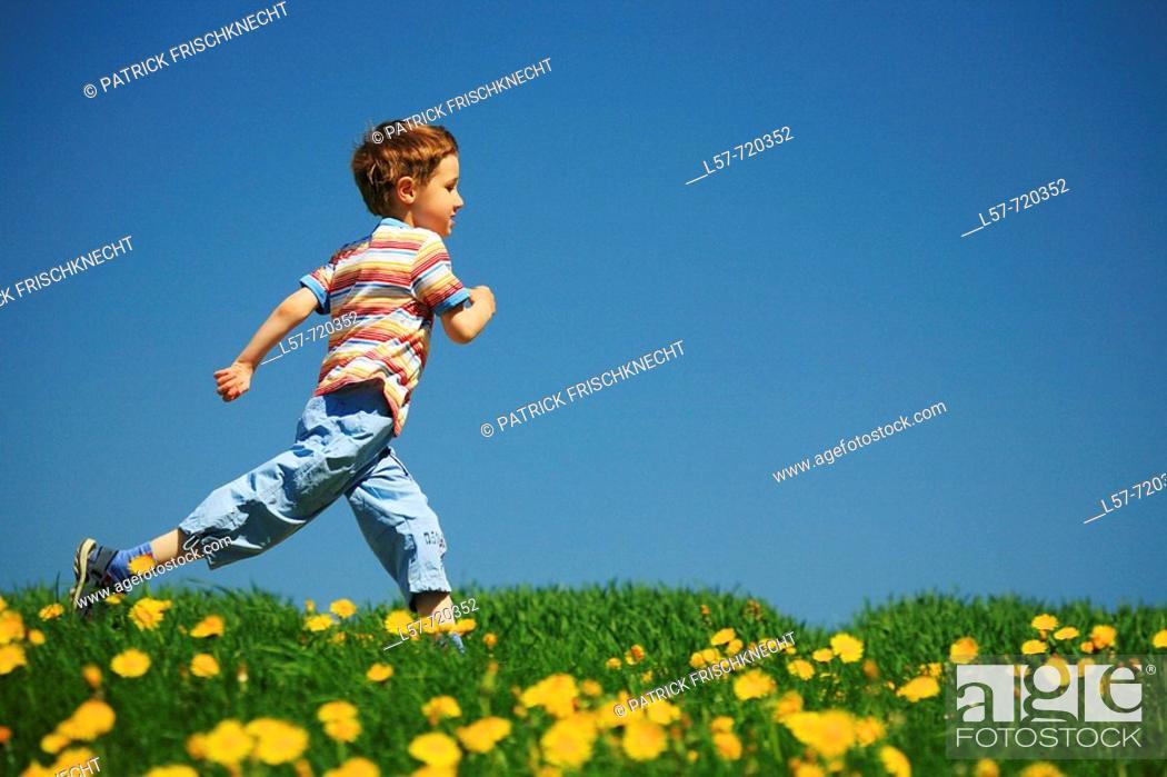 Stock Photo: Boy running through filed of Dandelions, in spring, Switzerland.