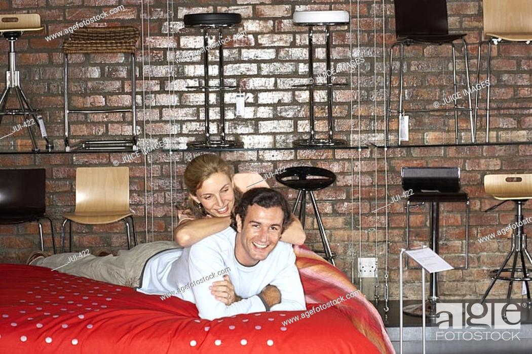 Stock Photo: Couple shopping in furniture store, lying on new bed, smiling, portrait.