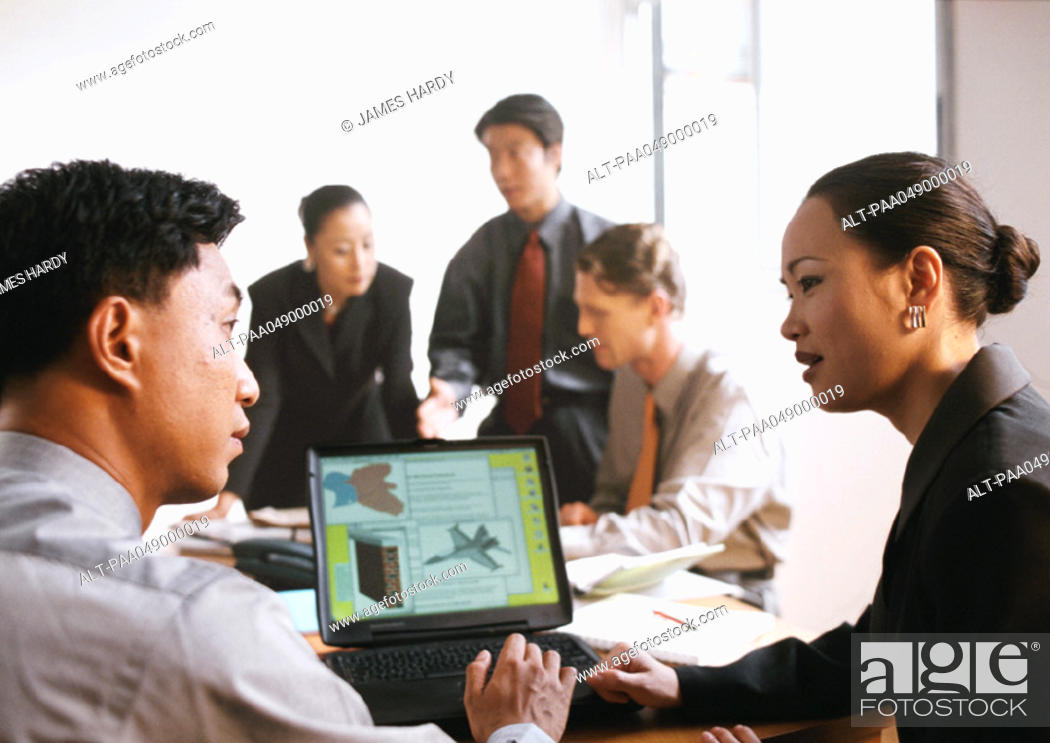 Stock Photo: Businessman and woman in front of computer screen, three people in background.