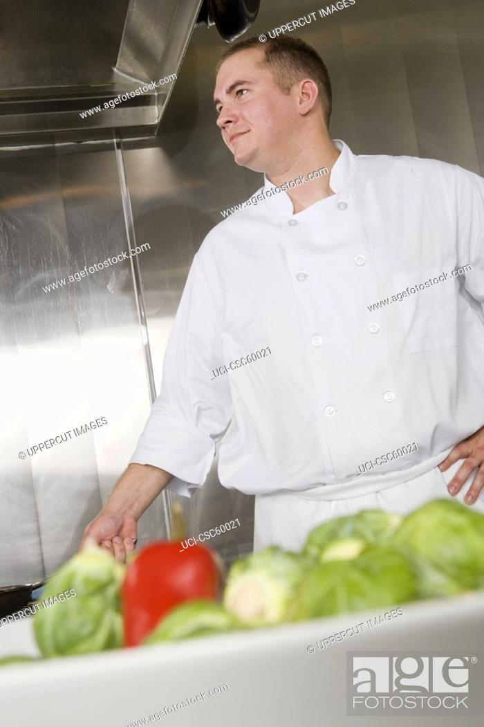 Stock Photo: Male chef with vegetables in foreground.
