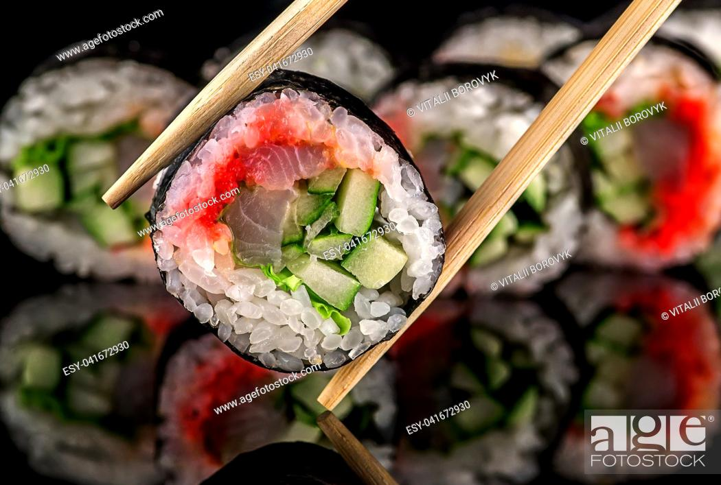 Stock Photo: Roll spicy lollo-Ross on black background with reflection. Blurred background.